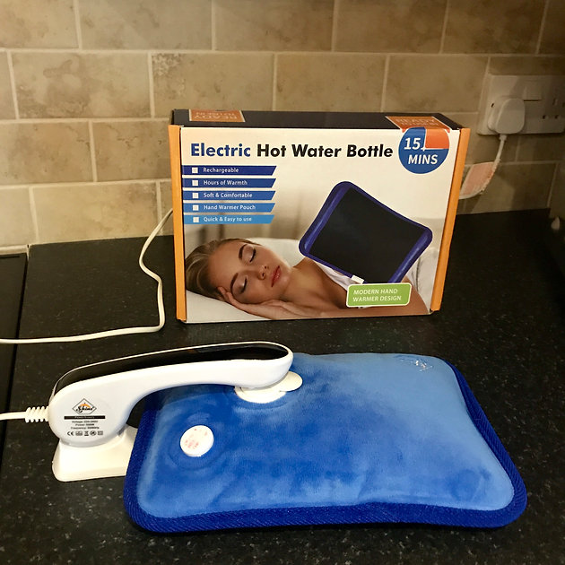 Blue hot water bottle plugged into mains charger