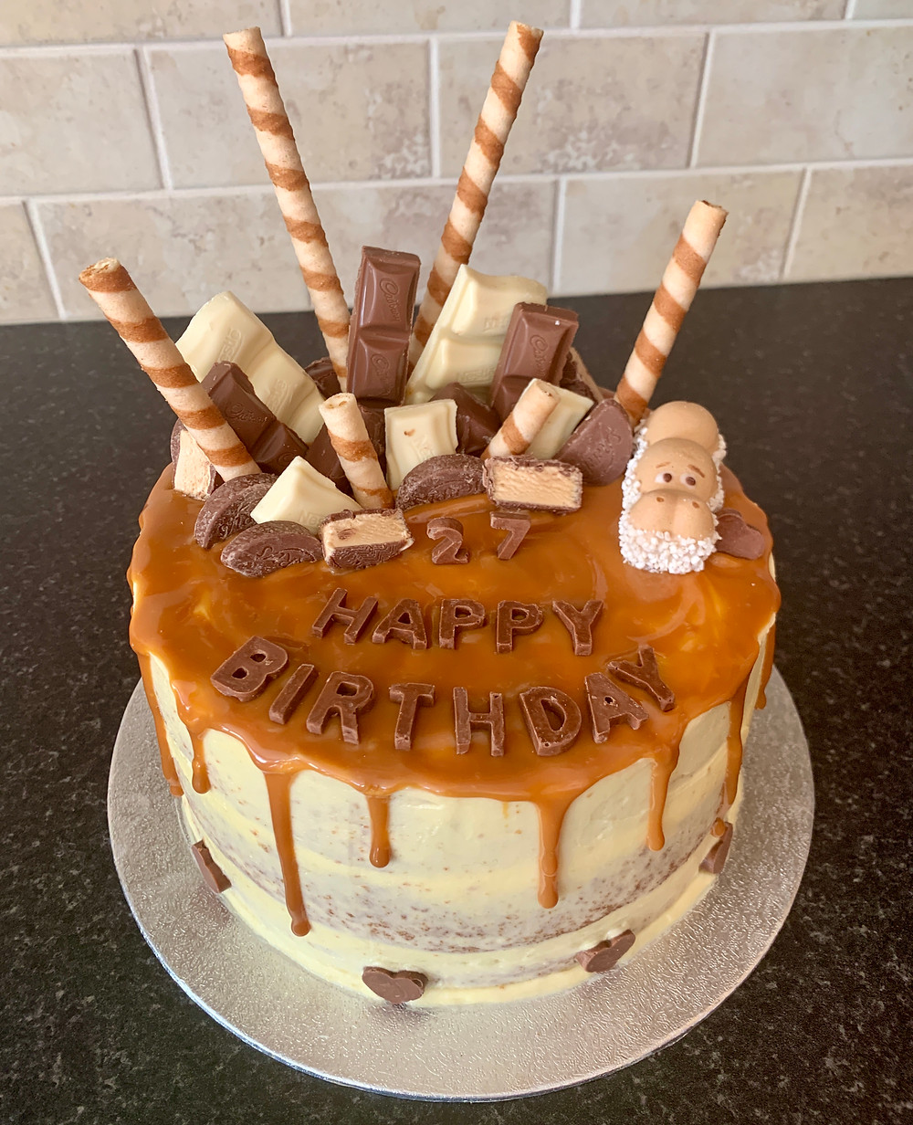 Birthday cake decorated with caramel sauce dripping and a selection of white and milk chocolate on top