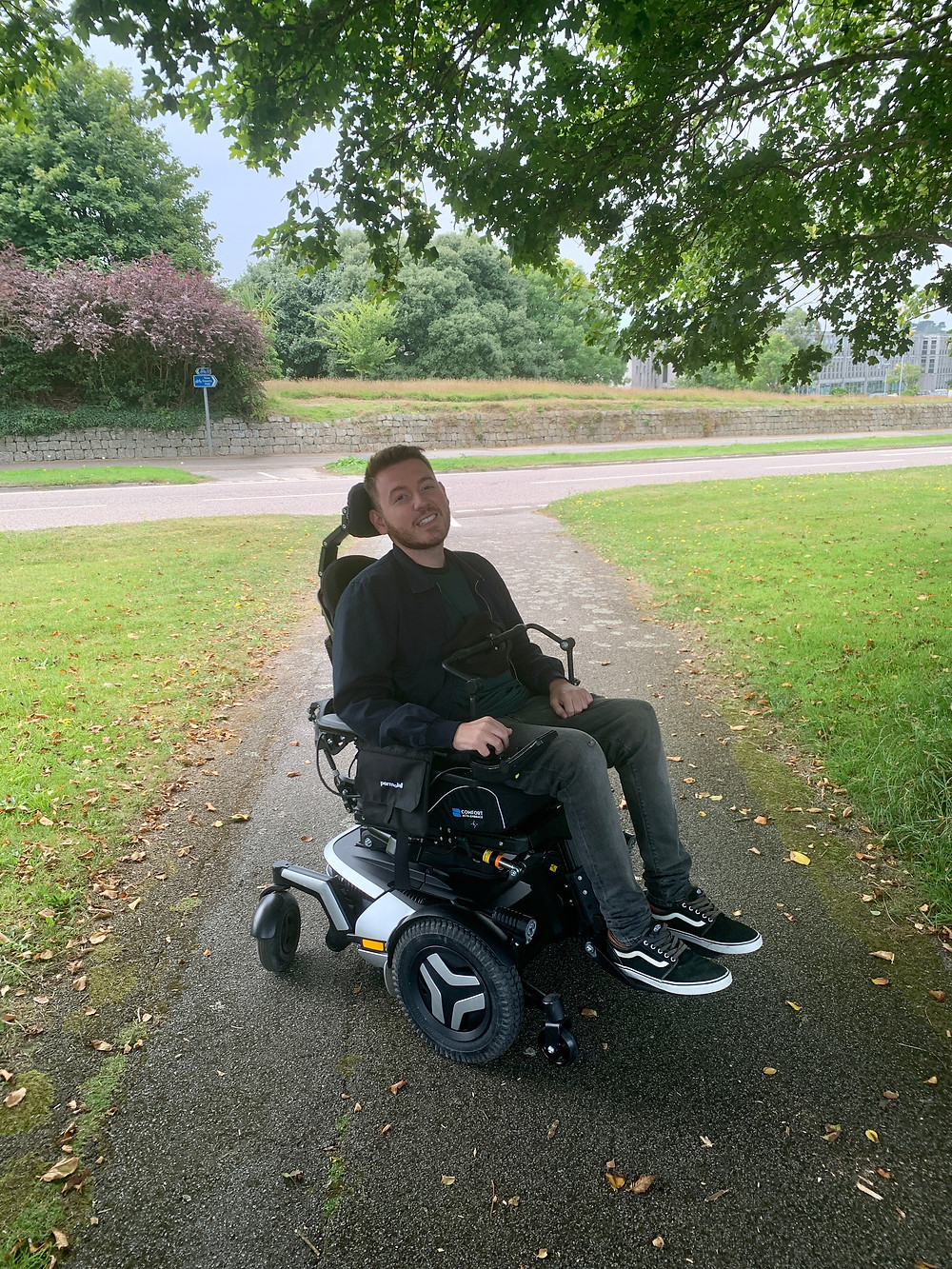 Ross using the power chair out on a walk, greenery in the background
