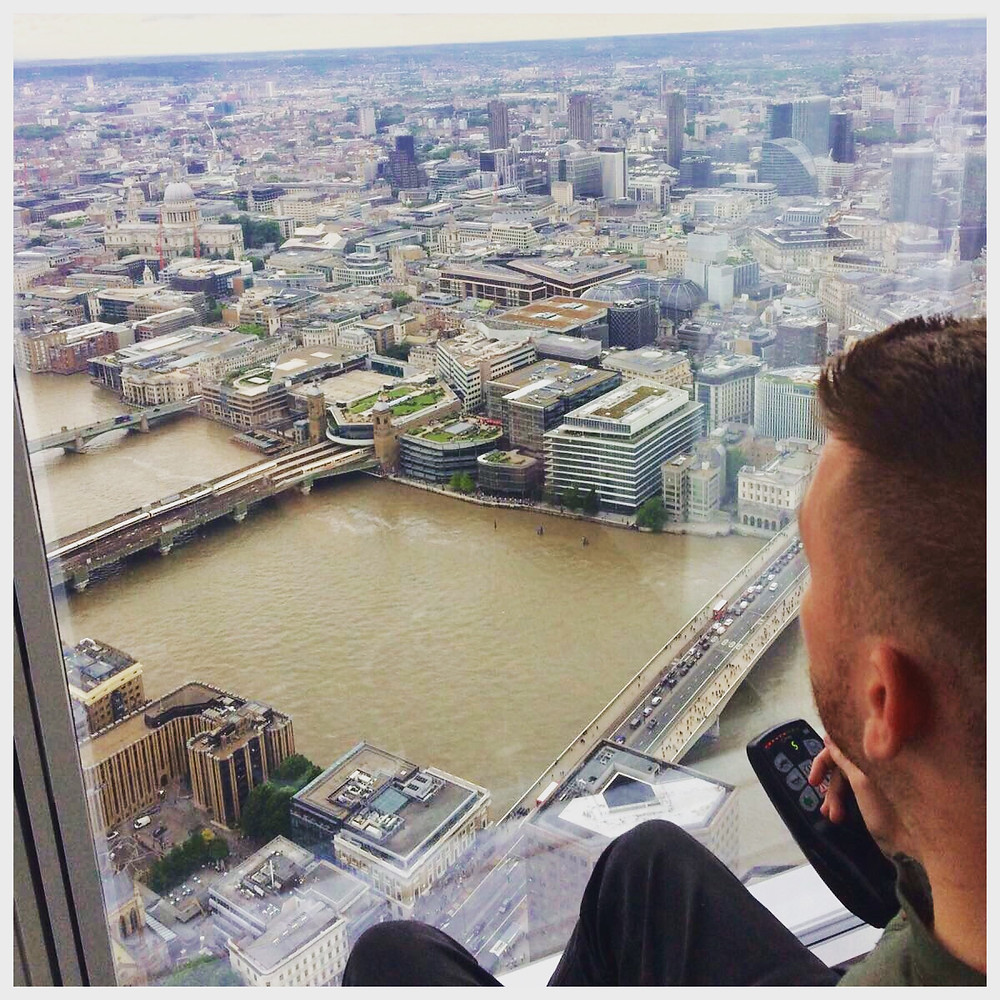 Ross looking out of the glass window at The Shard, rooftop views over London