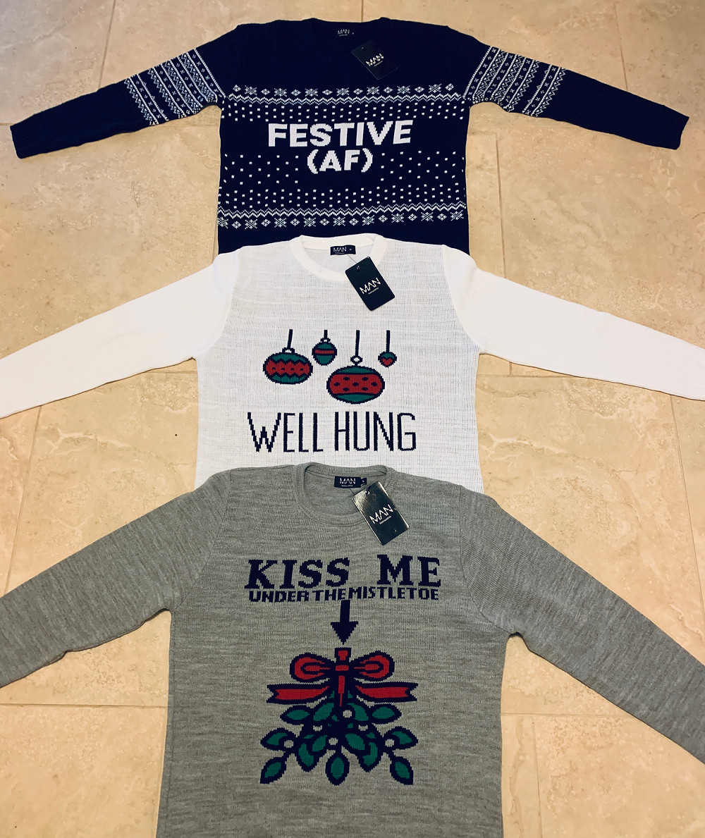 "3 christmas jumpers laid on the floor. One navy jumper with the text ""Festive AF"", one white jumper with a bauble and text saying ""well hung"" and one grey jumper with the text ""Kiss me under the mistletoe', with the missile pictures above the mans waist"