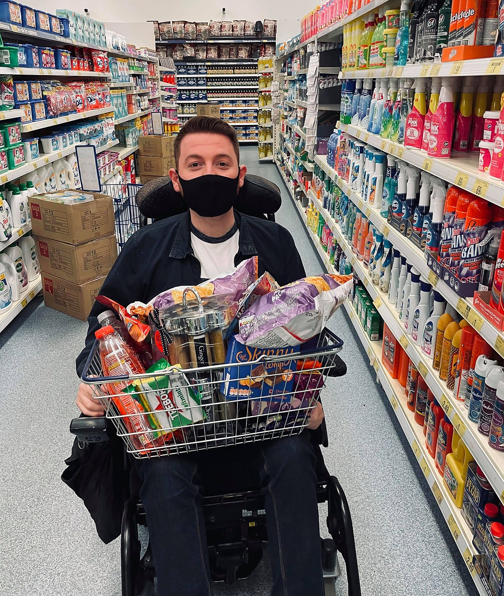 Ross sat in the B&M aisle with a basket full on his lap. Wearing a black face mask