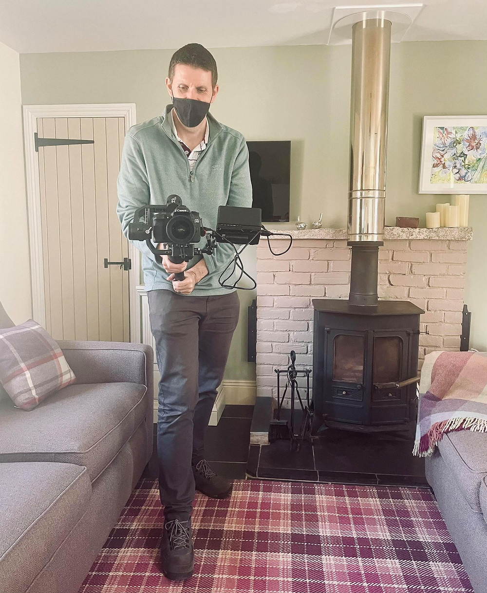 Behind the scenes shot of Neil holding a big recording camera filming Ross