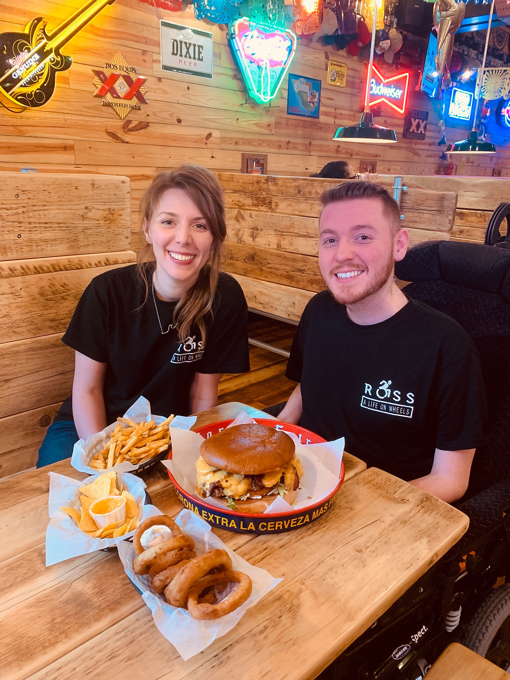 Ross and his sister smiling, surrounded by a table of food