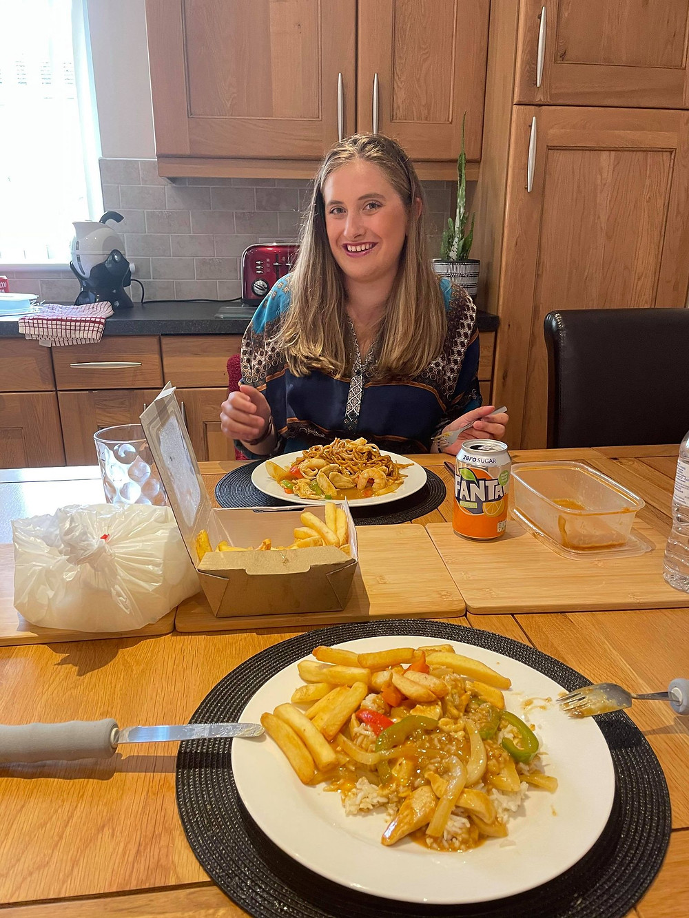 Ross's freind Sophie smiling with her takeaway - chicken satay with chips and rice
