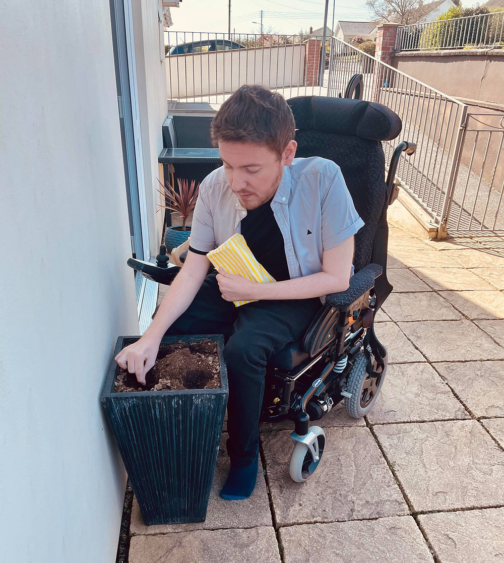 Ross outside holding a bag of soil whilst planting sunflower seeds