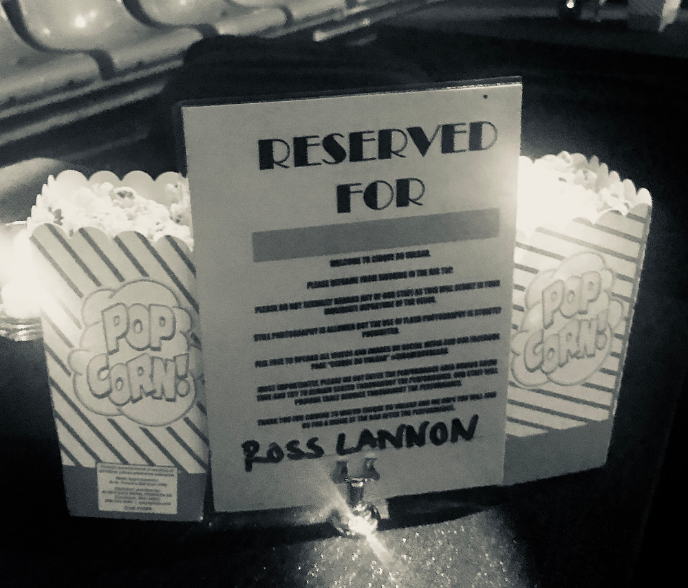 A reserved sign with Ross's name on, next to two portions of popcorn - VIP table seats