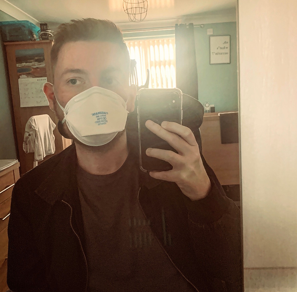 Selfie of Ross in the mirror, wearing a safety mask