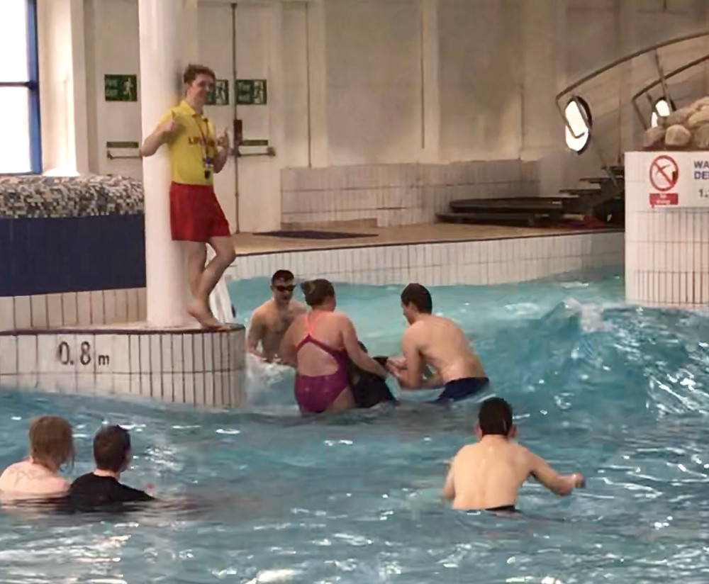 Photo of Ross being held above the water by two people whilst the wave machine is on