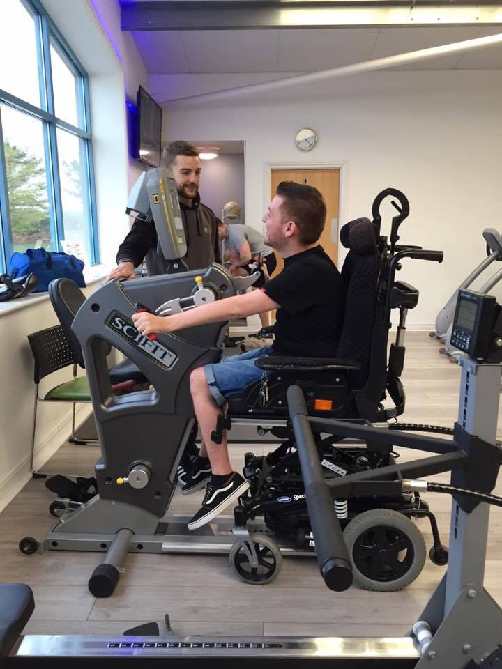 Ross at the gym on a hand pedal bike with his instructor