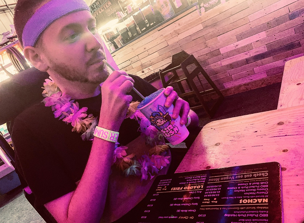 Ross wearing a Hawaiian neck garland, whilst sipping on his Slush drink
