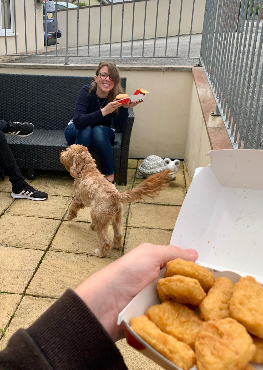 Ross's wrist holding a box of nuggets, with his sister in the background with a big mac burger