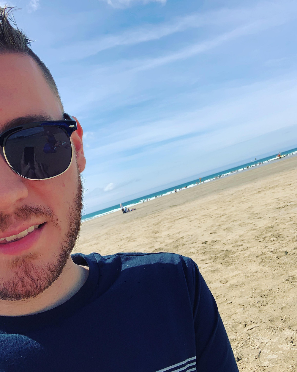A half-face selfie of Ross on the beach with sea views in the background
