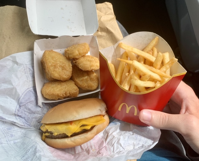 Ross's McDonalds order placed on his lap, showing 6 chicken nuggets, a cheeseburger and fries