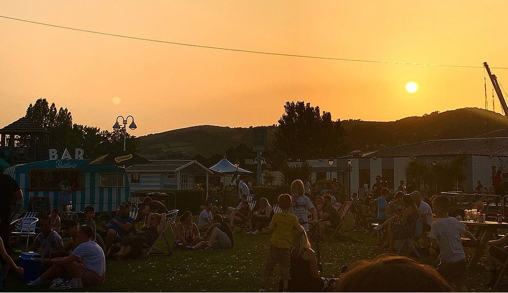 Sunset photo, showing the crowds of people chilling on grassed area