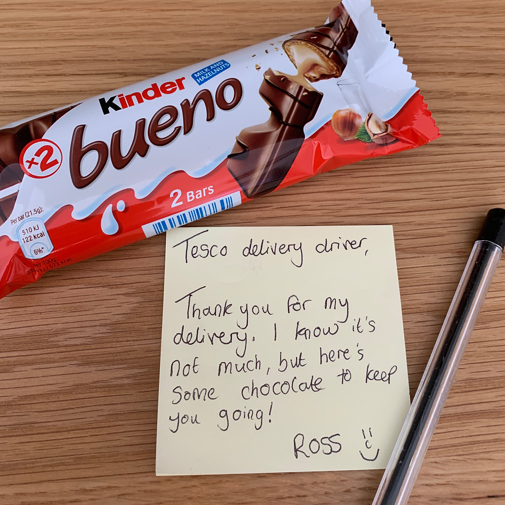 A kinder bueno chocolate bar with a post-it note attached saying thank you to the Tesco delivery driver