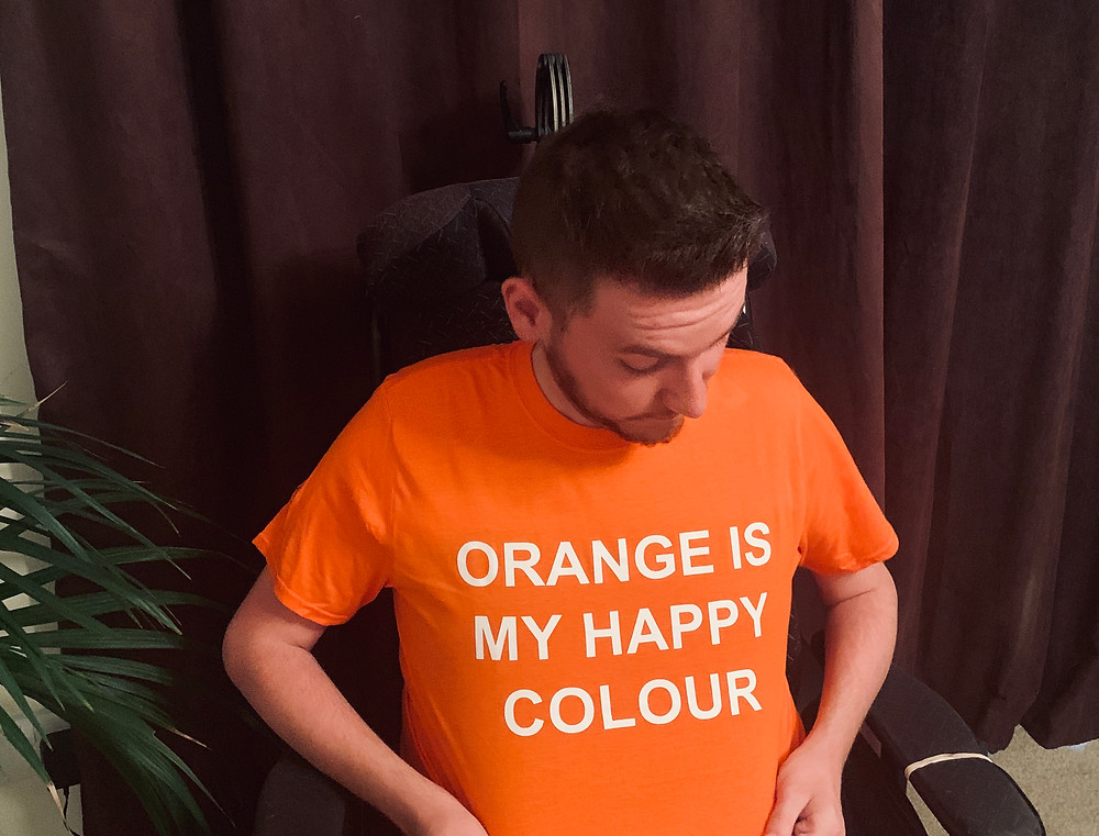 "Ross looking down at his bright orange t-shirt with the text: ""orange is my happy colour"""