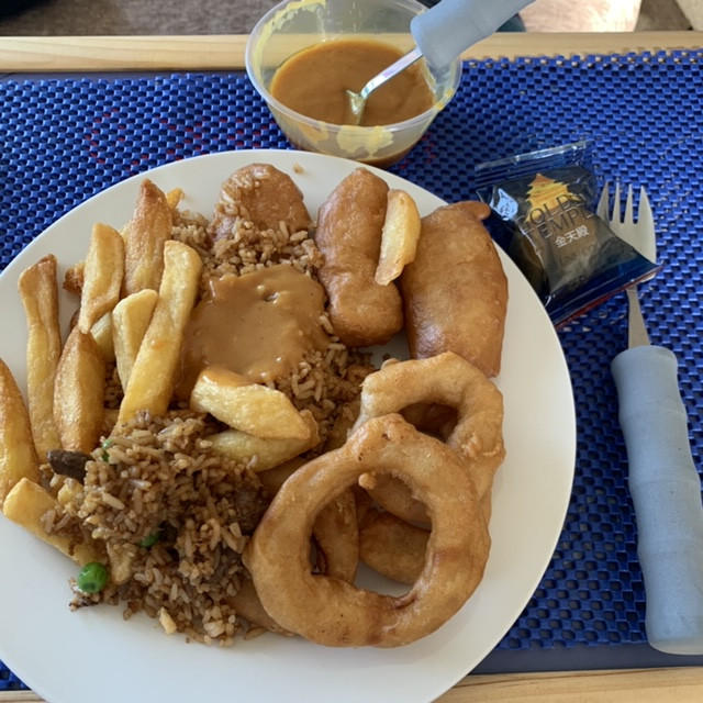 Chinese takeaway - chicken balls, curry sauce, chips, rice and onion rings