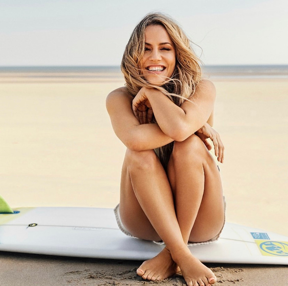 Shot of Caroline Flack sat on a surfboard on the beach, smiling with the sand between her toes