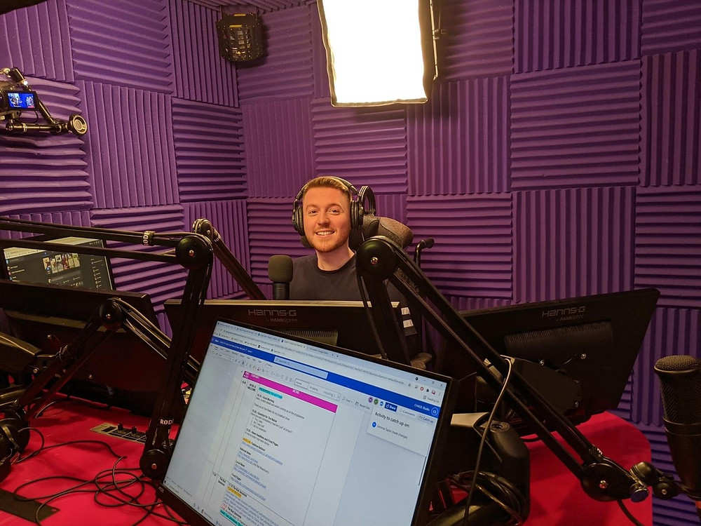 Ross wearing headphones sat in his wheelchair behind the radio desk. In a booth with purple soundproof walls