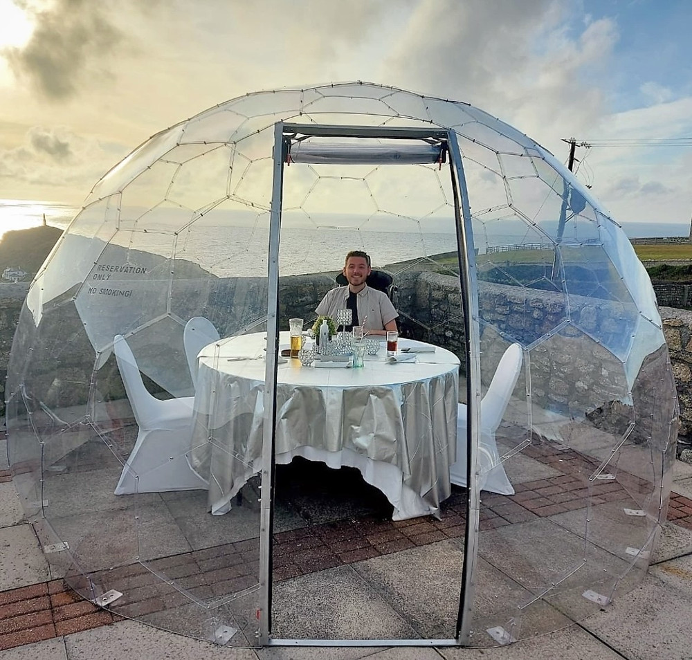 Ross sat outside at a table inside in a large, clear dome - overlooking the sea