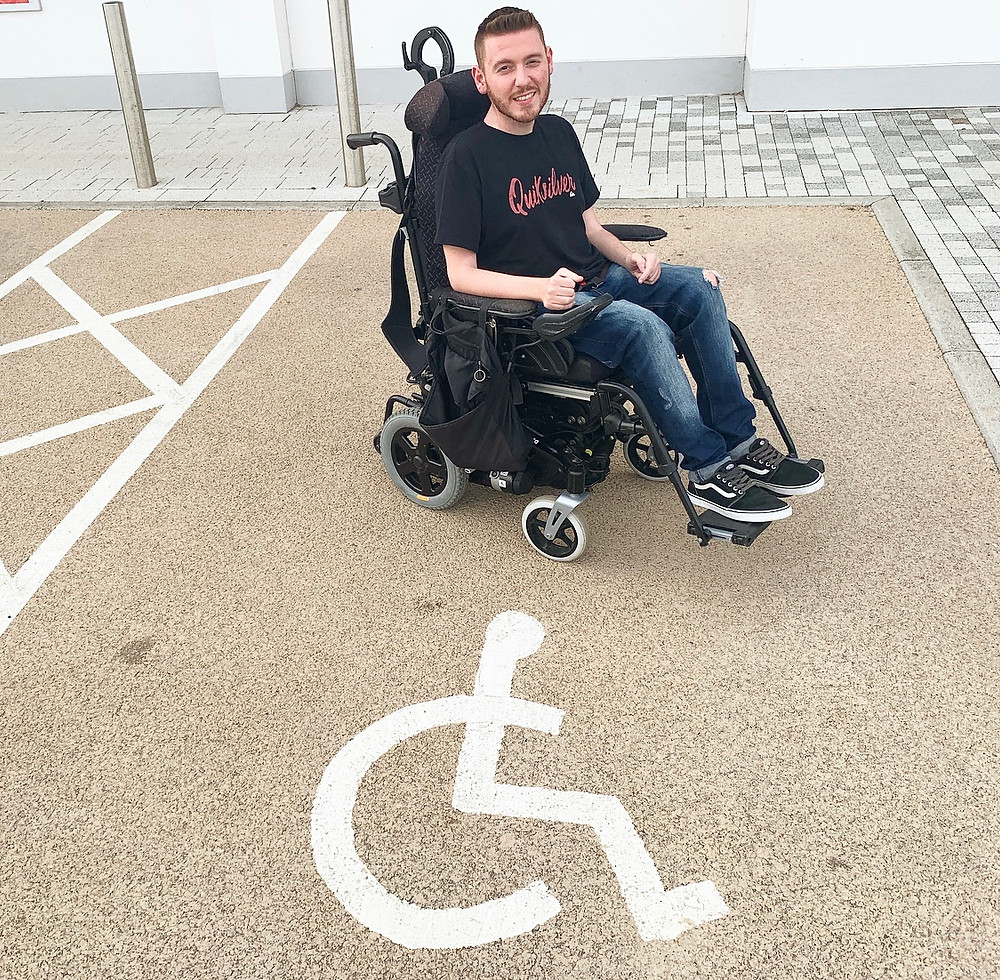 Ross sat in his wheelchair, next to a disabled parking bay