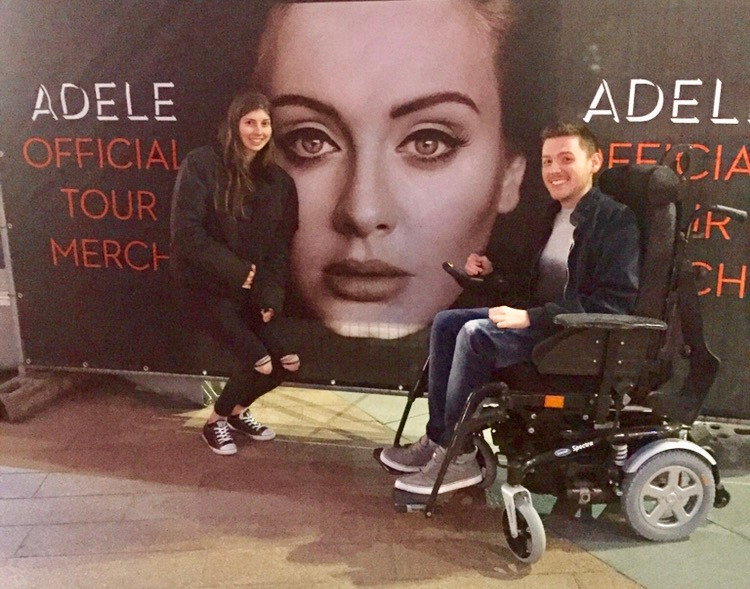 Ross & his friend beside a large Adele merchandise sign