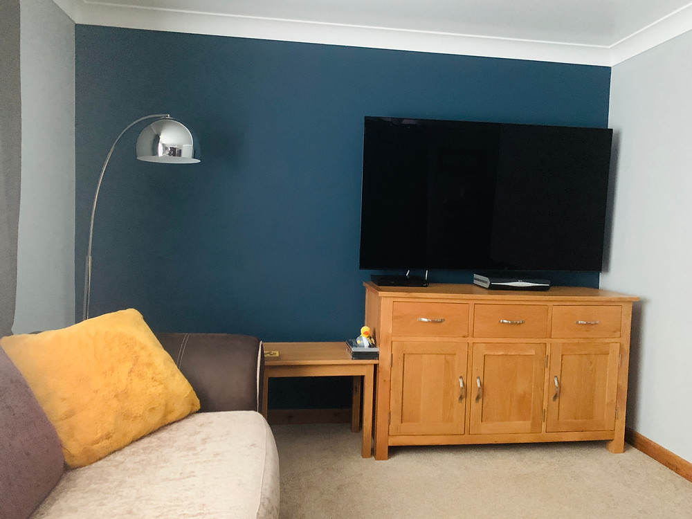 Ross's lounge showing a freshly painted navy feature wall, with surrounding grey walls and large TV
