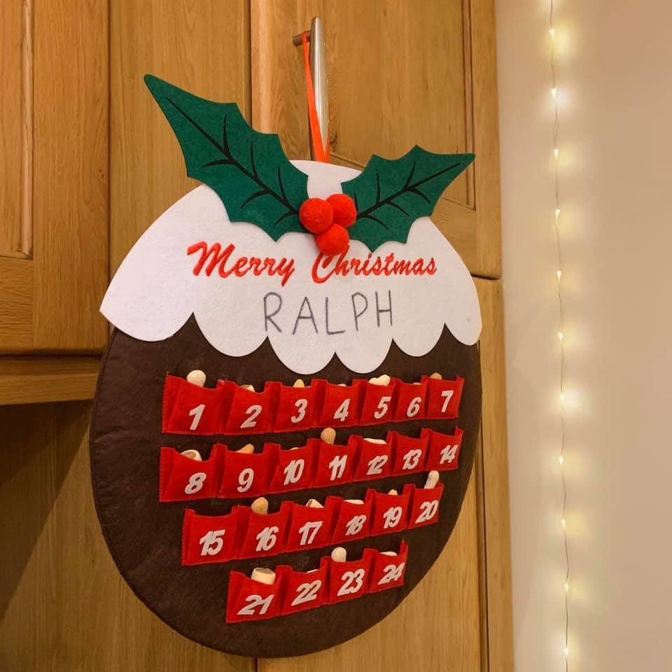 "A christmas pudding shaped advent calendar, filled with dog treats. Text says ""merry christmas Ralph"" at the top of the pudding"