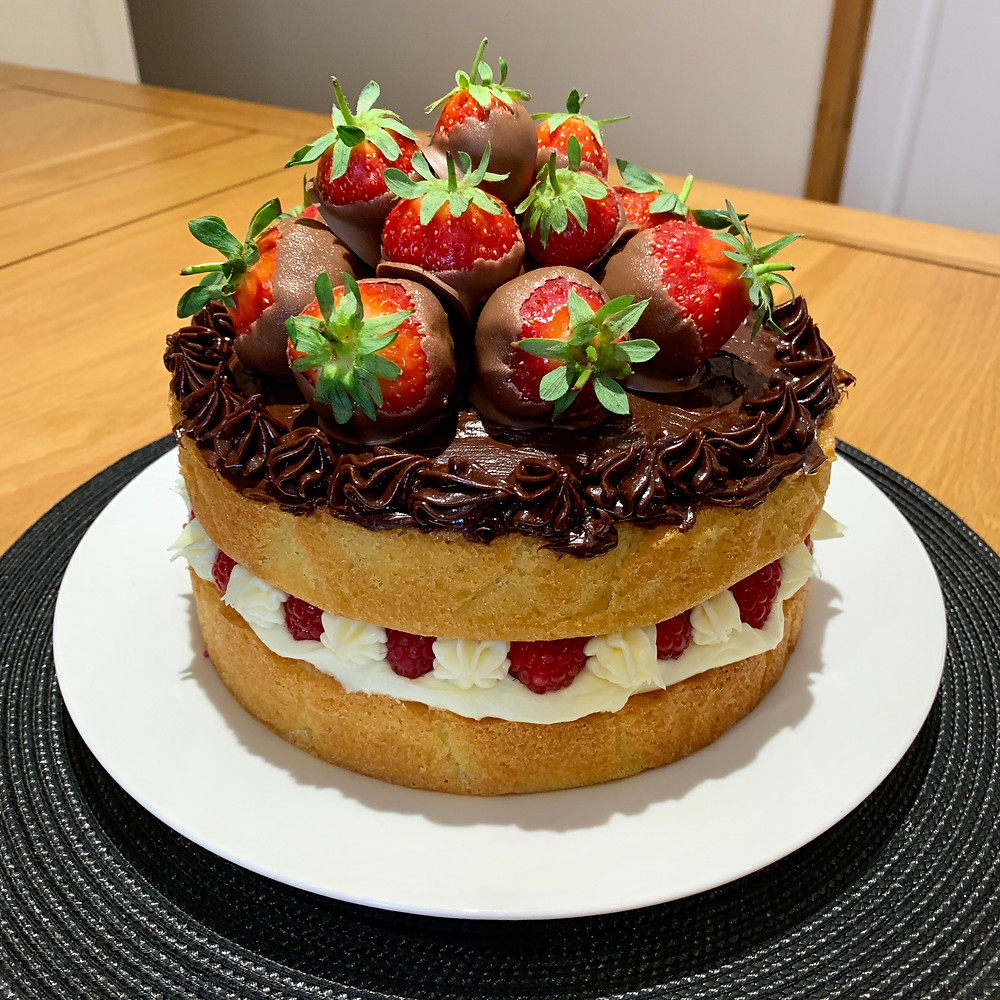 A vanilla sponge cake topped with chocolate strawberries