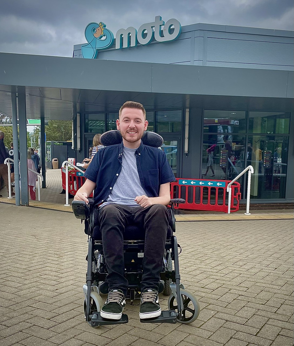 Ross sat in his wheelchair, outside the main entrance sign for Exeter service station
