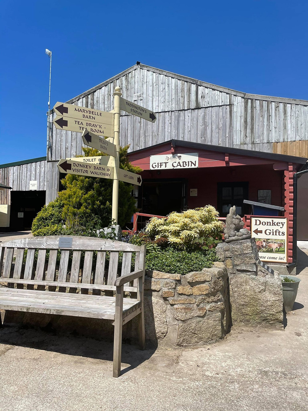 Outside view of the gift shop, with a bench and sign posts pointing you to the right directions