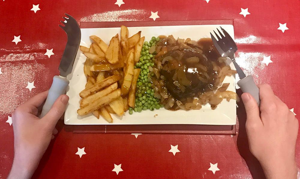 A shot of Ross's dinner (hamburger steak, chips and peas) holding a lightweight knife and fork