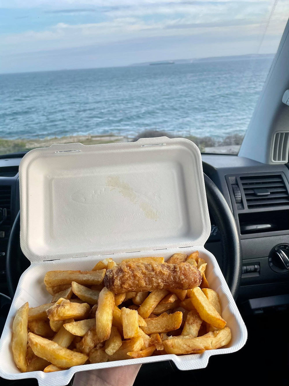 View from the drivers seat, Ross's wrist holding a tray of sausage and chips with the sea in the background