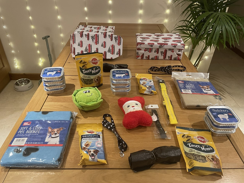 Contents of Ross's shoebox played out on his kitchen table. Showing dog food pouches, toys, treats, poo bags, leads, collars and blankets.