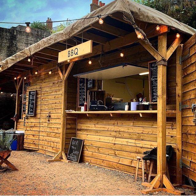 Wooden bar area with 'BBQ' sign and lightbulb style string lights