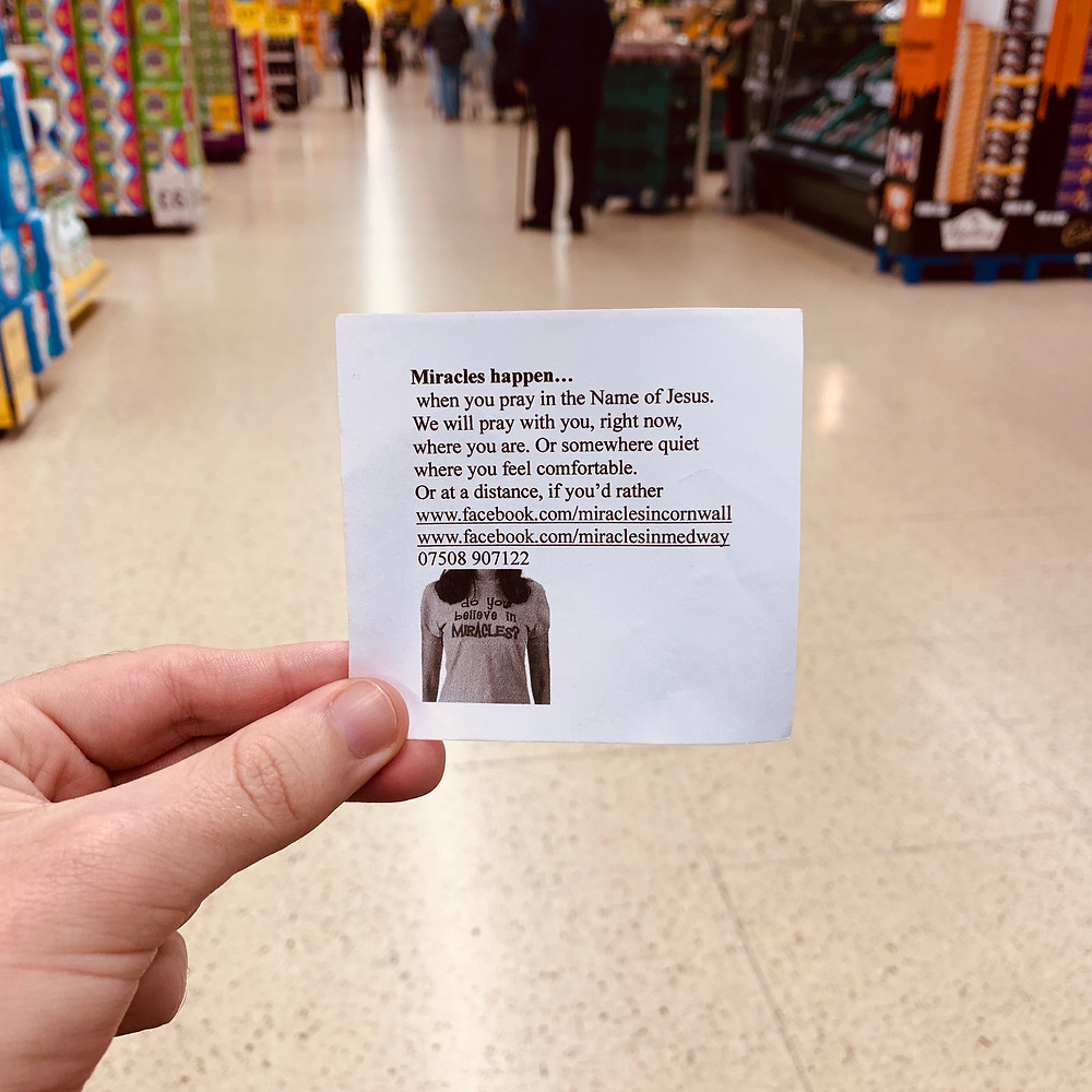 "A shot of Ross's hand, holding a small piece of paper in Tesco, with the text: ""Miracles happen when you pray in the name of Jesus"". Followers by a mobile number and Facebook page details"