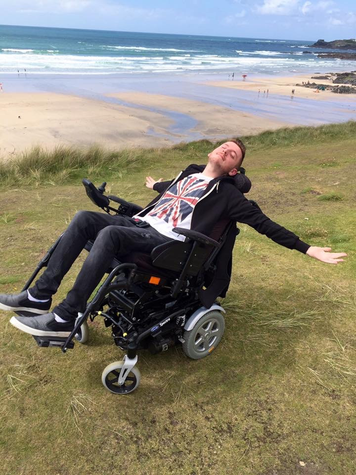 Ross reclined back in his wheelchair, arms out, whilst say on the clif top - surrounded by blue seas and sky