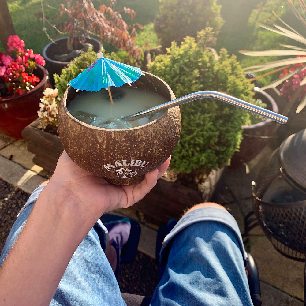 Ross's hand holding a coconut shaped cup filled with alcohol and a metal straw