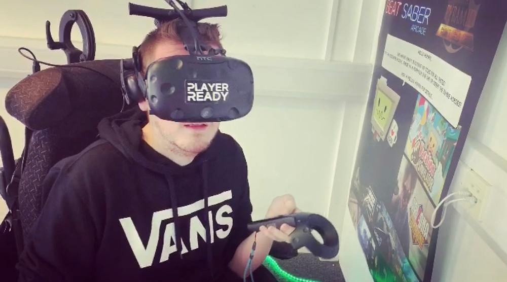 Ross wearing a virtual reality headset, covering his ears and ears - holding a remote control