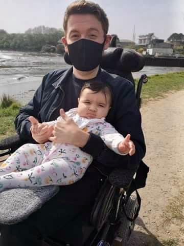 Ross sat in the park wearing a black mask, holding his friends baby
