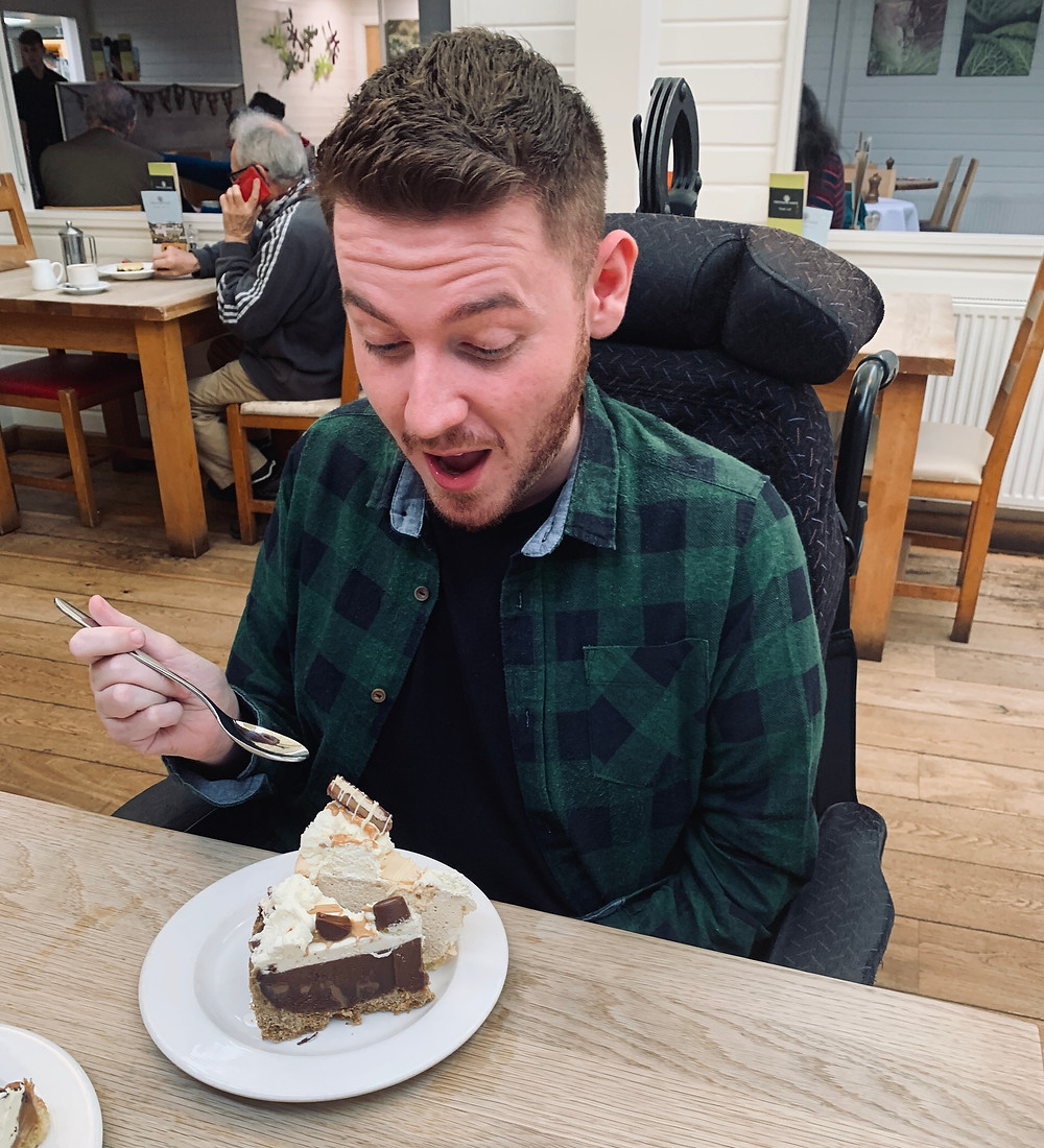 Ross holding a spoon, looking down at his plate with two cheesecake puddings - mouth open.