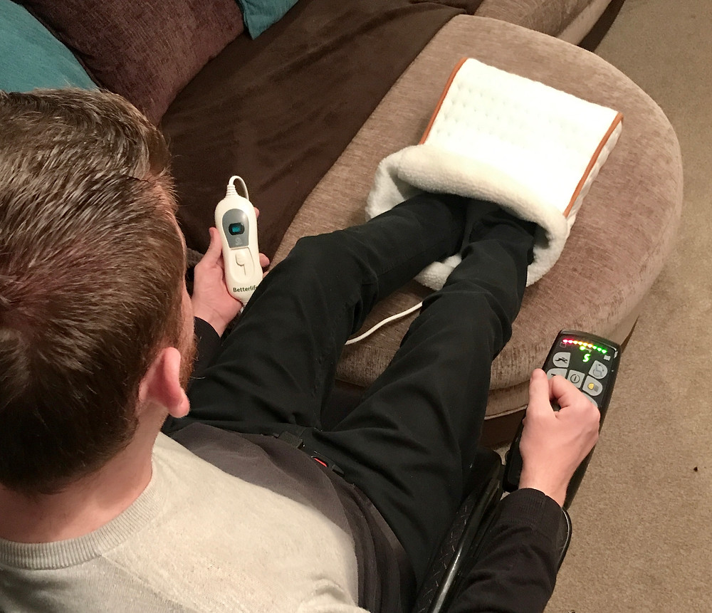 An aeriel shot of Ross with his feet in the foot warmer, holding the temperature control