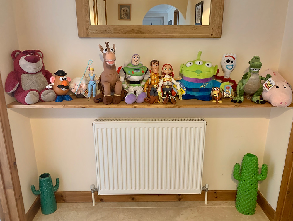 A wooden shelf in Ross's hallway showing off his large collection of Toy Story teddies