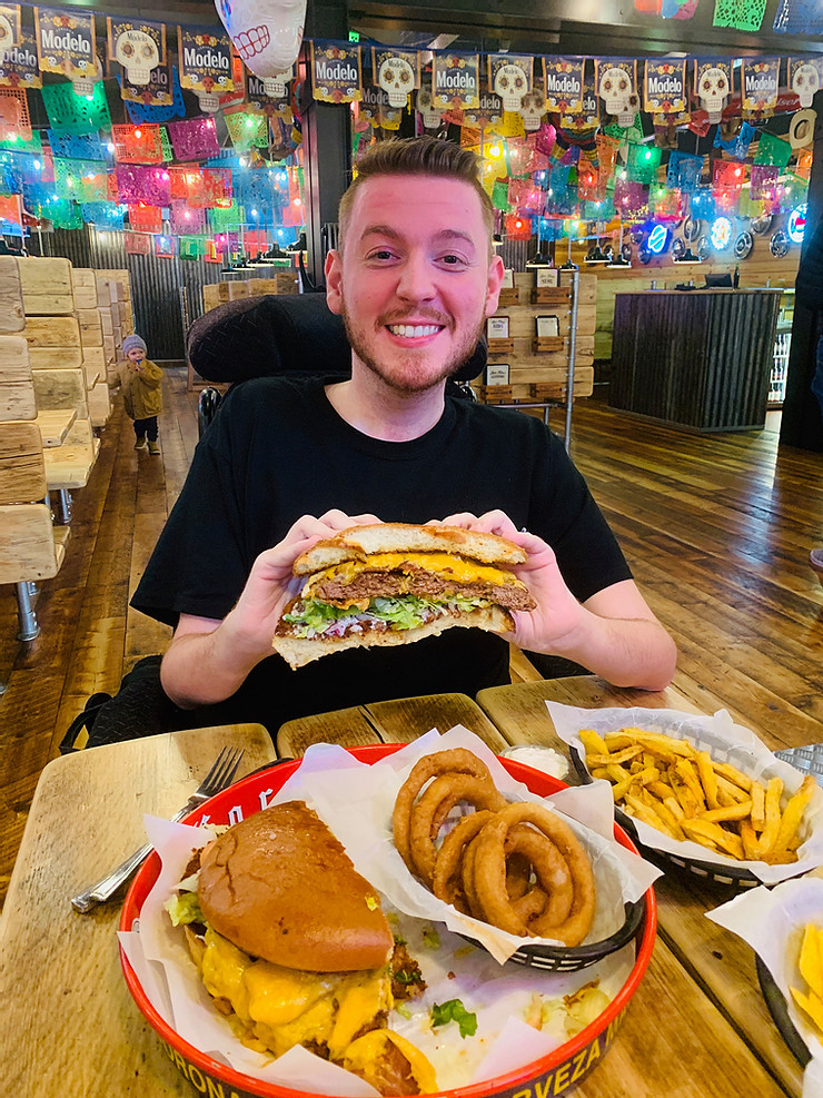 Ross holding a ginormous burger, surrounded by a table of chips and onion rings