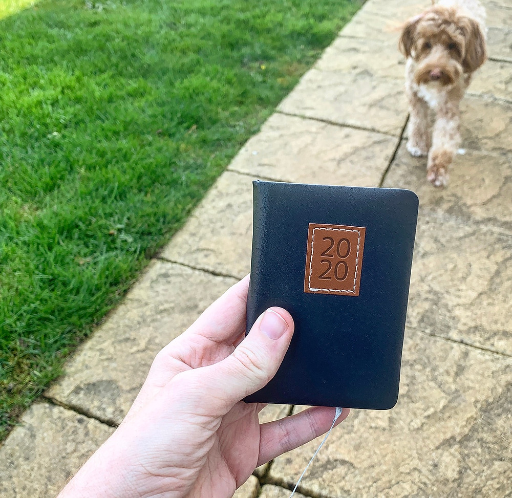 Ross' wrist holding a miniature 2020 diary, in the garden with his dog in the background