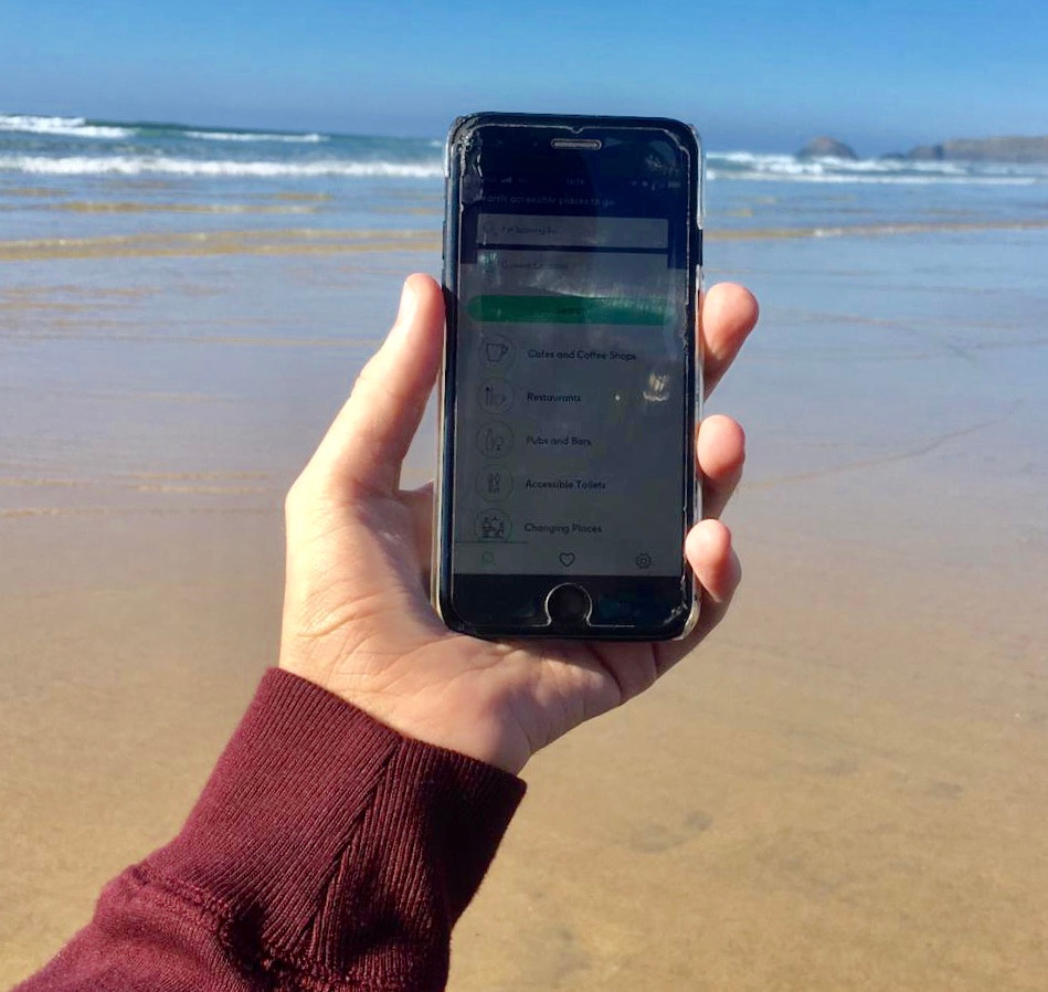 Ross holding his phone at the beach, with the AccessAble app open, sea views in the background