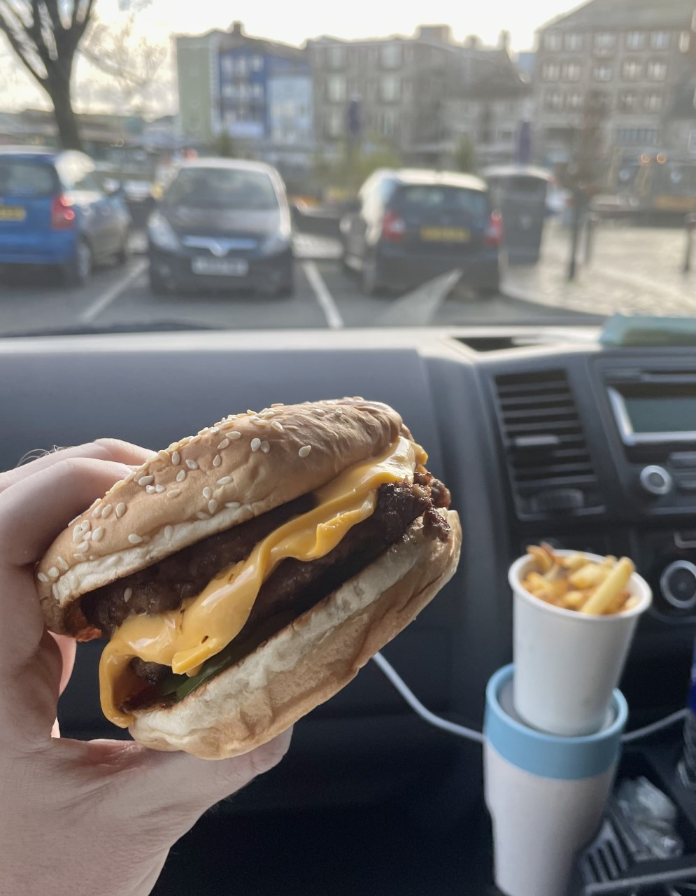 Close up shot of Ross's wrist holding his burger, sat inside the car