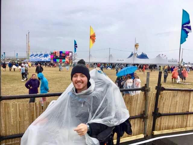 Ross at a festival, wearing a bobble hat and poncho