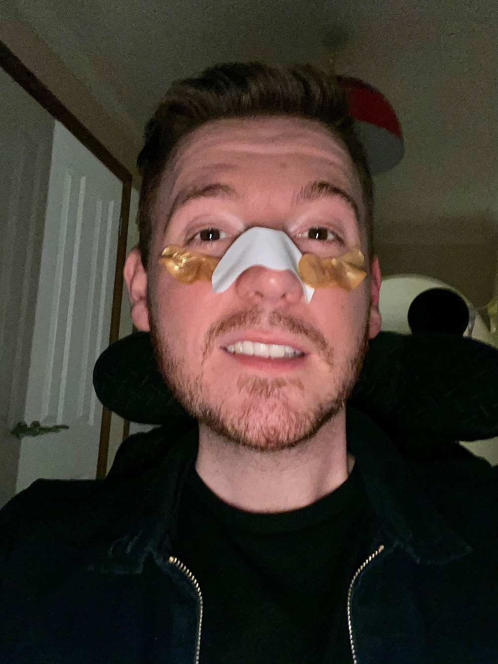 selfie of Ross with a nose strip on his face and two gold eye patches